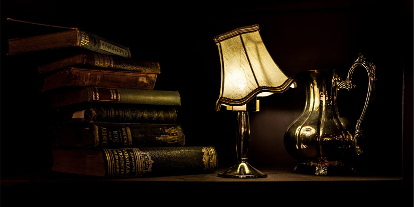 pile of old books with a lamp on a table in a dark room