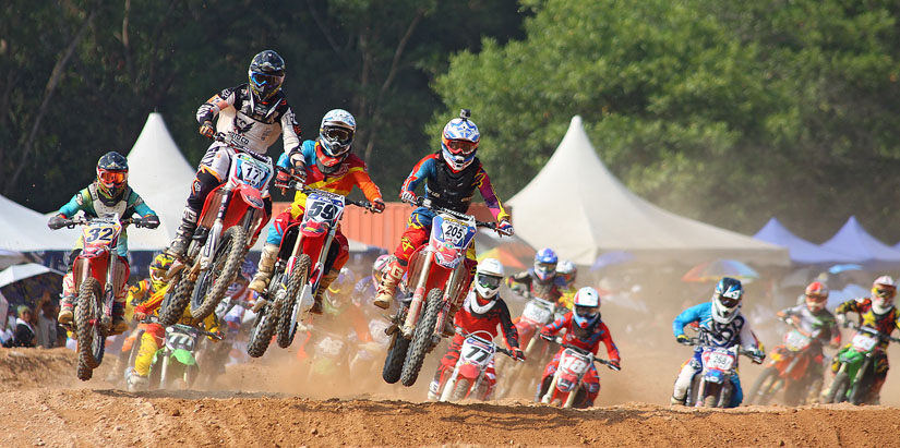 Dirt bikers racing on track in daylight