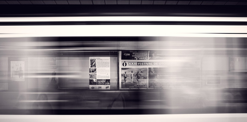 Poster ads in an underground railway platform in black and white