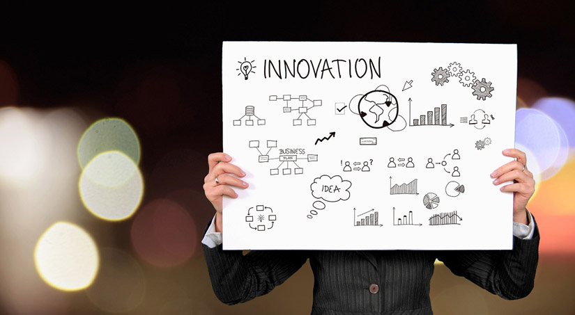 A woman holding a sign with a drawn marketing plan and the word 'Innovation' on it